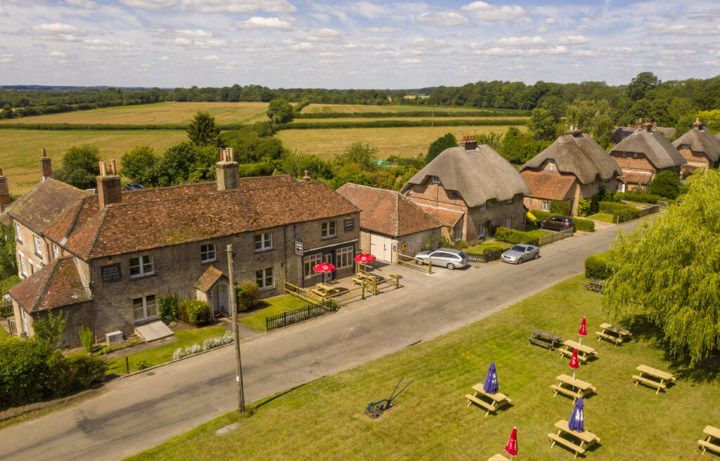 A photograph of East Stratton including the Northbrook Arms and thatch cottages.
